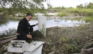 In a Friday, Sept. 22, 2017 photo, Erika Huddleston paints along Waco Creek for an exhibit that will open Nov. 9 at Art Center Waco. Huddleston has spent the last couple of months the creek that rambles through South and Central Waco has long been overgrown with brush and marred with litter and old rubble. It has been paved or diverted in places. But mostly it has been ignored. (Jerry Larson/Waco Tribune-Herald via AP)