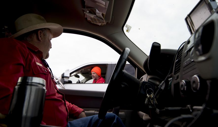 In this Monday, Sept. 25, 2017 photo, Scott Werbelow, supervisor of the Cody Region game wardens for the Wyoming Game and Fish Department, chats with a hunter from the front seat of his state truck while he checks on area hunters near Meeteetse, Wyo. (Mark Davis/The Powell Tribune via AP)