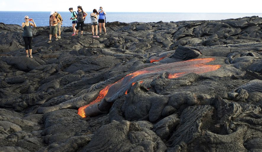 FILE - In this Monday, Aug. 8, 2016 file photo, visitors look at lava from Kilauea, an active volcano on Hawaii's Big Island, as it flows toward the ocean in Hawaii Volcanoes National Park near Kalapana, Hawaii. Hawaii residents and an organization representing federal workers filed a lawsuit against the Federal Aviation Administration on Wednesday, Oct. 4, 2017 seeking to force it to do something about tour helicopters buzzing their communities and national parks across the country.  (AP Photo/Caleb Jones, File)