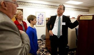 In this March 24, 2015, photo, State Rep. Mike Braun, R-Jasper, right, shows Marvin and Vicky Eisenhut, of Haysville, Ind., and their grandson Cooper Uebelhor of Ferdinand, 12, his office at the Indiana Statehouse in Indianapolis. The little-known but independently wealthy Indiana state lawmaker is plunging roughly $800,000 into his GOP Senate primary bid. Braun says he also raised another $200,000 from donors during the fundraising quarter that ended Sept. 30.  (The Herald via AP)