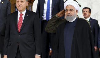 Turkish President Recep Tayyip Erdogan, left, with Iranian President Hassan Rouhani, right, reviews an honour guard during an official arrival ceremony at the Saadabad Palace in Tehran, Iran, Wednesday, Oct. 4, 2017.  (Kayhan Ozer/Pool Photo via AP)