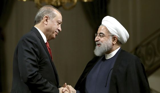 Iranian President Hassan Rouhani, right, and Turkish President Recep Tayyip Erdogan shake hands at the conclusion of their joint press conference at the Saadabad Palace in Tehran, Iran, Wednesday, Oct. 4, 2017. With Turkey's president by his side, Iranian President Hassan Rouhani pledged Wednesday that they would ensure borders in the region remain unchanged after the recent Kurdish independence referendum in Iraq. (AP Photo/Ebrahim Noroozi)