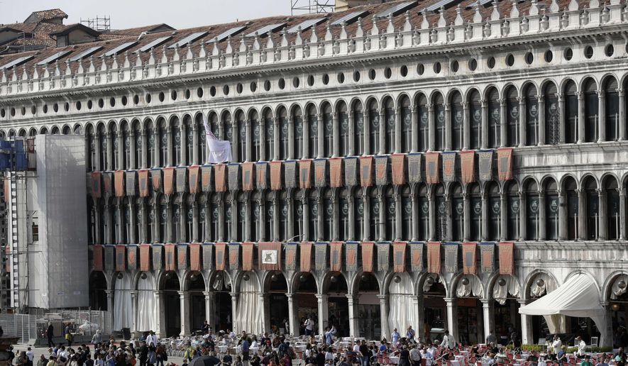 Tourists walk in St Mark's square in Venice, Italy, Wednesday, Oct. 4, 2017. British architect David Chipperfield is bringing his expertise in restoring historic buildings to the 500-year-old Procuratie Vecchie building on the northern edge of St. Mark's Square, which will house a new initiative to help disadvantaged people around the globe. (AP Photo/Luca Bruno)