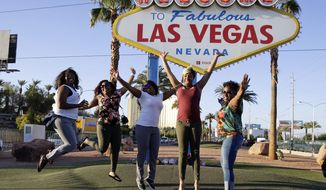 In this Tuesday, Oct. 3, 2017 photo, tourists pose for photos in front of the Welcome to Las Vegas sign that has flowers honoring the people who died in a mass shooting on Sunday in Las Vegas. But even though the city is in mourning, for many it is business as usual with celebrations and parties continuing. (AP Photo/Chris Carlson)