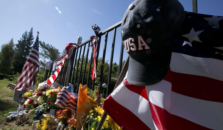 An USA hat hangs from a flag that makes up part of a memorial on the backyard fence of Las Vegas shooting victim Kurt Von Tillow Wednesday, Oct. 4, 2017, in Cameron Park, Calif. Von Tillow, 55, was at Sunday's concert with his wife, daughter, son-in-law and other family members when the shooting started, KCRA reported. (AP Photo/Rich Pedroncelli)