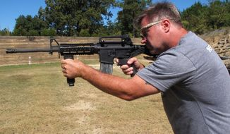 "Shooting instructor Frankie McRae aims an AR-15 rifle fitted with a ""bump stock"" at his 37 PSR Gun Club in Bunnlevel, N.C., on Wednesday, Oct. 4, 2017. The stock uses the recoil of the semiautomatic rifle to let the finger ""bump"" the trigger, making it different from a fully automatic machine gun, which are illegal for most civilians to own. (AP Photo/Allen G. Breed)"