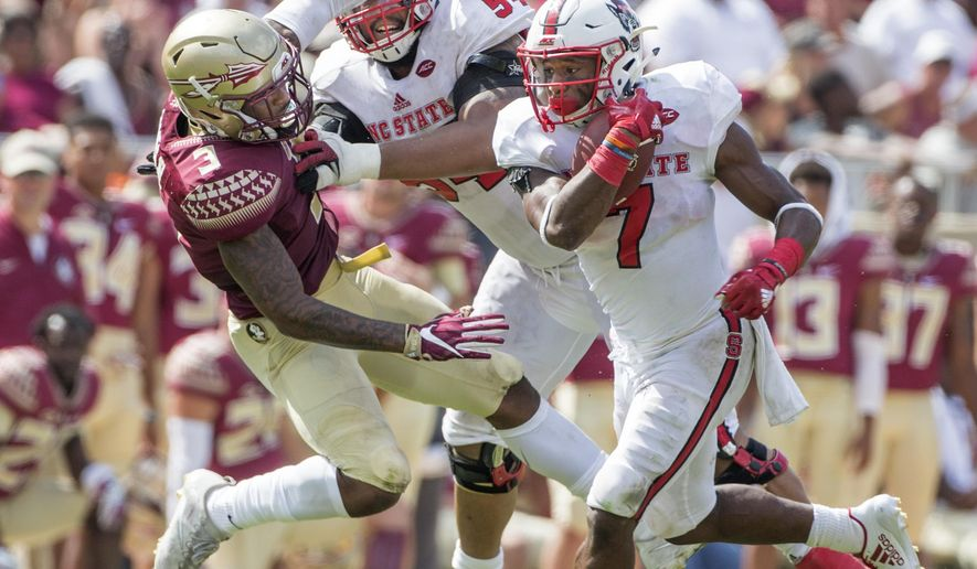 FILE - In this Sept. 23, 2017, file photo, North Carolina State running back Nyheim Hines picks up extra yardage as teammate tackle Will Richardson blocks Florida State defensive back Derwin James in the second half of an NCAA college football game in Tallahassee, Fla. Hines and the 24th-ranked Wolfpack are ranked in the AP Top 25 for the first time since 2010. They take on No. 17 Louisville on Thursday, Oct. 5. (AP Photo/Mark Wallheiser, File)