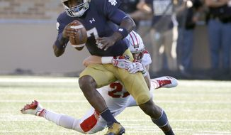 Notre Dame quarterback Brandon Wimbush breaks out of the grasp of Miami (Ohio) defensive back Matt Merimee during the first half of an NCAA college football game Saturday, Sept. 30, 2017, in South Bend, Ind. (AP Photo/Charles Rex Arbogast)