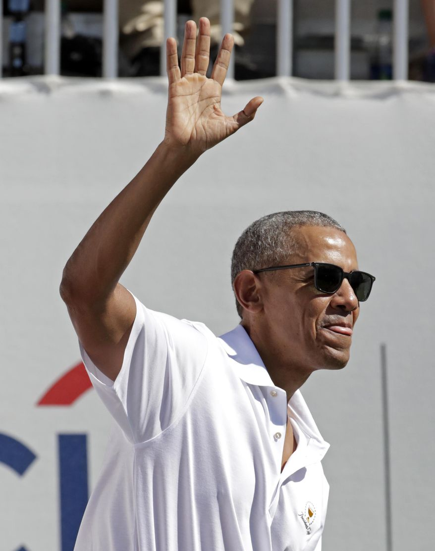 Former President Barack Obama waves to spectators before the first round of the Presidents Cup at Liberty National Golf Club in Jersey City, N.J., Thursday, Sept. 28, 2017. (AP Photo/Julio Cortez)