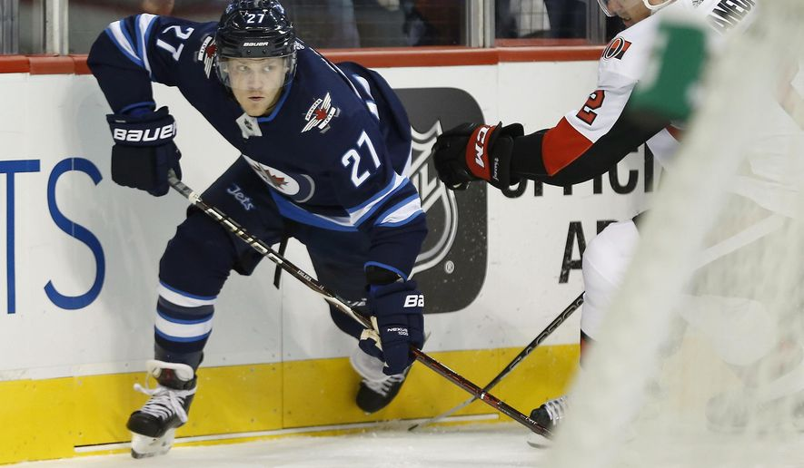 FILE - In this Sept. 27, 2017, file photo, Winnipeg Jets' Nikolaj Ehlers (27) drives out of the corner as Ottawa Senators' Dion Phaneuf (2) defends during the second period of an NHL preseason hockey game in Winnipeg, Manitoba. The Jets agreed to terms on a $42 million, seven-year contract extension with Ehlers on Wednesday, Oct. 4, 2017.  (John Woods/The Canadian Press via AP, File)