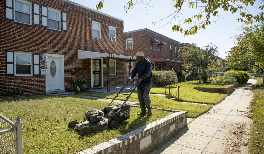 Johnny Wilson, a friend of the property owner, mows the lawn in Washington, Wednesday, Oct. 4, 2017, where a late-night party that turned a vacant home into something resembling a strip club will be at the center of arguments before the Supreme Court.  The court is being asked to decide whether police had sufficient reason to arrest the group.  (AP Photo/Andrew Harnik)