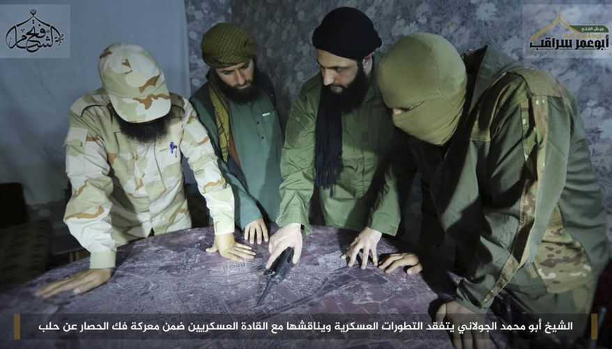 """FILE -- This undated file photo, shows Abu Mohammed al-Golani, second right, then leader of Fatah al-Sham Front, in pictures posted by the group, discussing battlefield details with field commanders over a map, in Aleppo, Syria. Russia's military announced Wednesday, Oct. 4, 2017, that it carried out airstrikes in Syria this week that critically wounded al-Golani, the leader of the al-Qaida-linked Levant Liberation Committee and killed 12 other militant commanders. Writing in Arabic  banner reads, """"Sheik Abu Mohammed al-Golani inspects military development and discusses them with military commanders as part of the battle for lifting the siege off Aleppo."""" (Militant UGC via AP, file)"""