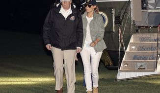 President Donald Trump and first lady Melania Trump walk across the South Lawn of the White House in Washington, Tuesday, Oct. 3, 2017, as they return from a trip to Puerto Rico in the wake of Hurricane Maria. (AP Photo/Pablo Martinez Monsivais)