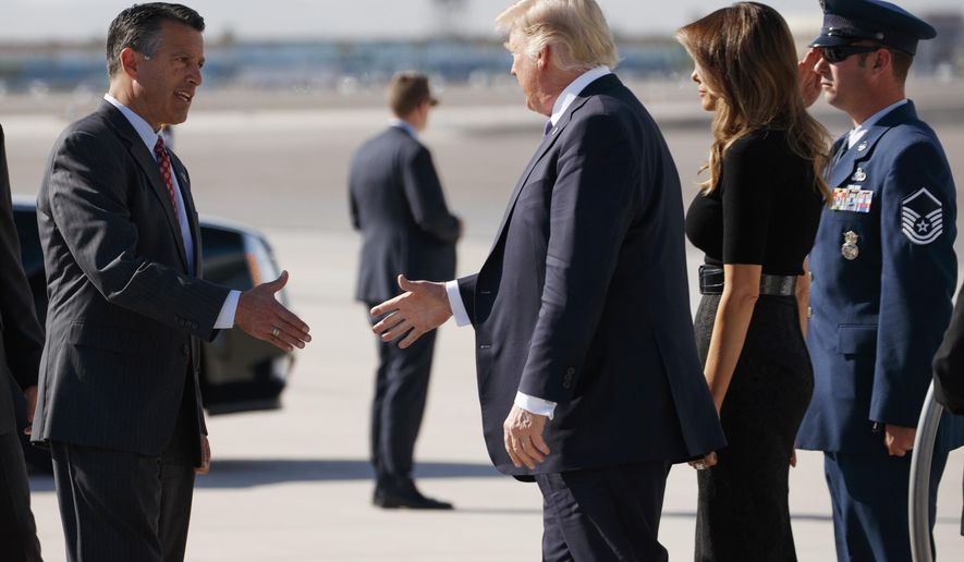Nevada Gov. Brian Sandoval, left, greets President Donald Trump and first lady Melania Trump as they arrive Wednesday, Oct. 4, 2017, at Las Vegas McCarran International Airport to meet with victims and first responders of the mass shooting. (AP Photo/Evan Vucci)