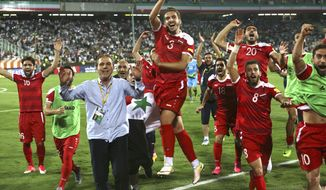 FILE - In this Sept. 5, 2017 file photo, Syria's national soccer team celebrates at the conclusion of their match with Iran which drew 2-2 during their Round 3 - Group A World Cup qualifier at the Azadi Stadium in Tehran, Iran.  Regardless of how Syria does in its World Cup playoff against Australia, the team has helped football knock fighting out the headlines for a while in their war-torn country. The Syrians are still in contention to qualify for the World Cup for the first time, and the journey to their biggest match so far has captured domestic and international attention.(AP Photo/Vahid Salemi, File)