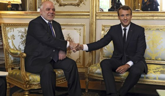 French president Emmanuel Macron, right, shakes hands with Iraqi Prime minister Haider al-Abadi prior to their meeting at the Elysee palace in Paris, Thursday, Oct. 5, 2017. Al-Abadi is meeting with French President Emmanuel Macron for talks on the international fight against Islamic State group extremists and rebuilding Iraq's economy.(Ludovic Marin, Pool via AP)
