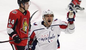 Washington Capitals left wing Alex Ovechkin (8) celebrates his third goal of the game as Ottawa Senators center Jean-Gabriel Pageau (44) skates behind  during the third period of an NHL hockey game in Ottawa, Ontario, Thursday, Oct. 5, 2017. (Adrian Wyld/The Canadian Press via AP)
