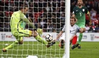 England's Harry Kane, center, scores the opening goal during the World Cup Group F qualifying soccer match between England and Slovenia at Wembley stadium in London, Thursday, Oct. 5, 2017. (AP Photo/Kirsty Wigglesworth)