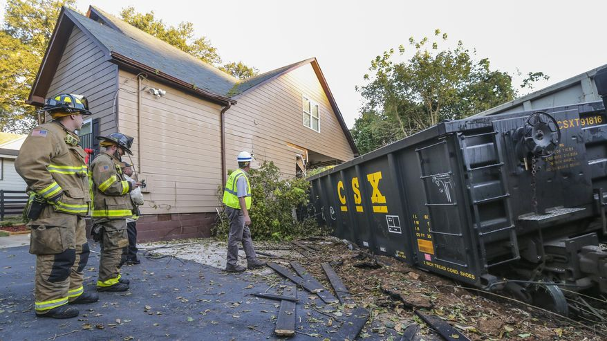 Emergency personnel work as the scene of a train derailment Thursday, Oct. 5, 2017, in Atlanta. Authorities say the freight train crashed into the bedroom of a home, sending a man inside to a hospital. (John Spink/Atlanta Journal-Constitution via AP)