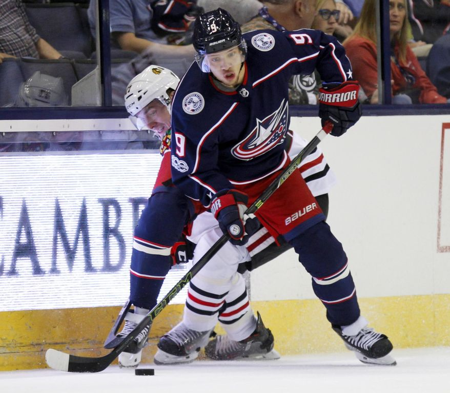 FILE - In this Sept. 19, 2017, file photo, Columbus Blue Jackets forward Artemi Panarin, right, of Russia, works for the puck against Chicago Blackhawks forward Laurent Dauphin during a preseason NHL hockey game in Columbus, Ohio. Panarin and rookie Pierre-Luc Dubois are among the newcomers who will skate for the Columbus Blue Jackets when they host the New York Islanders in the season opener Friday night.  (AP Photo/Paul Vernon)