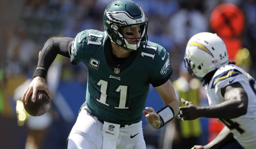 FILE - In this Sunday, Oct. 1, 2017 file photo, Philadelphia Eagles quarterback Carson Wentz scrambles during the first half of an NFL football game against the Los Angeles Chargers in Carson, Calif. Haason Reddick is coming home to go after Carson Wentz. The rookie linebacker returns to the field where he starred in college when the Arizona Cardinals (2-2) visit the Philadelphia Eagles (3-1) on Sunday, Oct. 8, 2017. (AP Photo/Jae C. Hong, File)