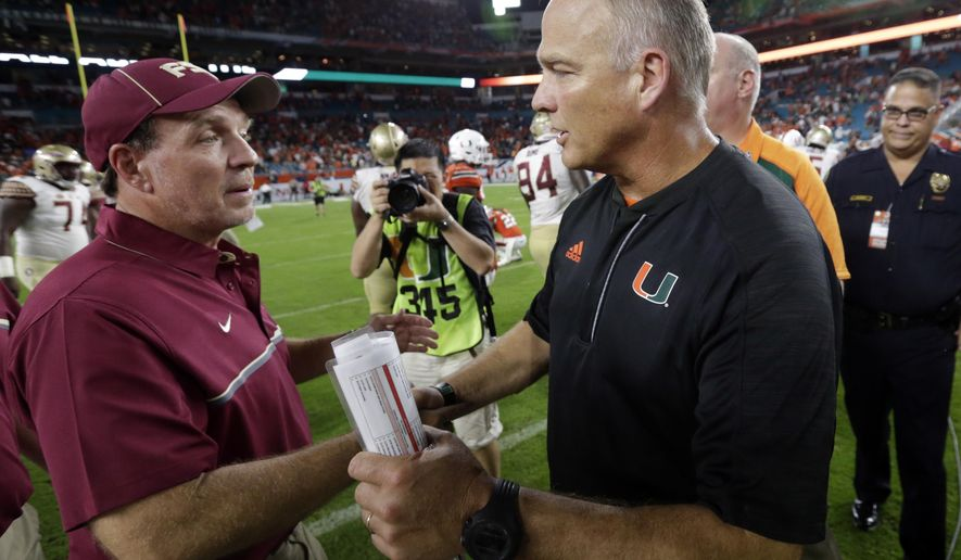 FILE - In this Oct. 9, 2016, file photo, Florida State head coach Jimbo Fisher, left, and Miami head coach Mark Richt meet after Florida State defeated Miami 20-19 in an NCAA college football game, in Miami Gardens, Fla. No. 13 Miami plays at Florida State on Saturday, Oct. 7, 2017. (AP Photo/Wilfredo Lee, File)