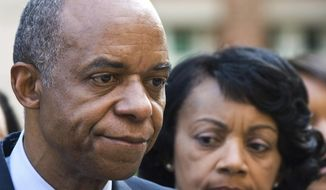 FILE - In this Wednesday, Aug. 5, 2009, file photo, former Louisiana congressman William Jefferson, left, stands outside the Albert V. Bryan Courthouse with his wife, Andrea after being convicted on 11 of 16 counts in Alexandria, Va. A federal judge has ordered that Jefferson, sentenced to 13 years in prison for taking bribes, be released from jail pending a new sentencing hearing. (AP Photo/Kevin Wolf, File)