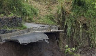 Workers observe a landslide on the outskirt San Jose, Costa Rica, Thursday, Oct. 5, 2017. Tropical Storm Nate formed off the coast of Nicaragua on Thursday and was being blamed for at least 17 deaths in Central America as it spun north toward a potential landfall on the U.S. Gulf Coast as a hurricane over the weekend. (AP Photo/Moises Castillo)