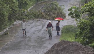 Neighbors walk under the rain past a washed out road in Alajuelita on the outskirts of San Jose, Costa Rica, Thursday, Oct. 5, 2017. Tropical Storm Nate formed off the coast of Nicaragua on Thursday and was being blamed for at least 17 deaths in Central America as it spun north toward a potential landfall on the U.S. Gulf Coast as a hurricane over the weekend. (AP Photo/Moises Castillo)