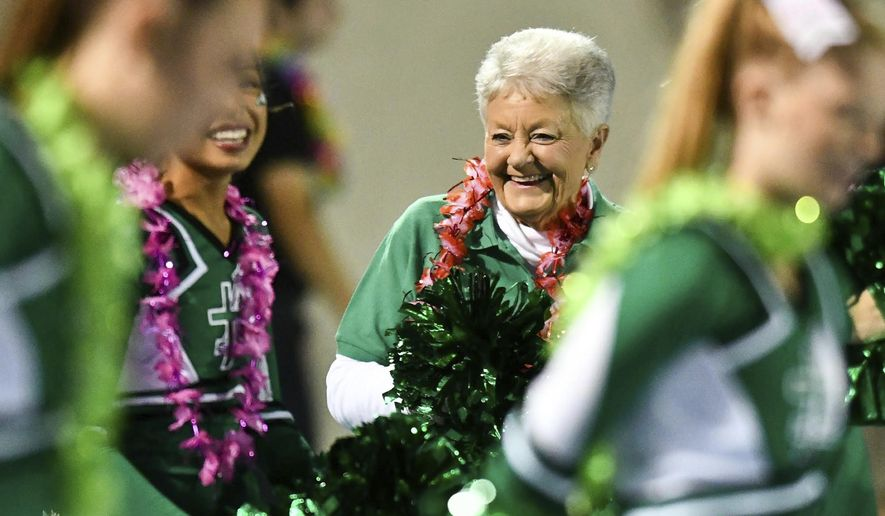 "In this Sept. 8, 2017 photo, Nancy Fischer, 79, cheers alongside the Alleman High School  cheerleaders 61 years after graduating from high school, during a game in Rock Island, Ill. As a youngster, Fischer had to pay her way through high school, $50 per year, so she took on as many babysitting jobs as time would allow. But the heavy workload kept her from an extracurricular activity she longed to be a part of. She wished she had the opportunity to be a cheerleader. So a friend bid on the ""Be an ""Honorary Cheerleader'' silent-auction package and won it for Fischer. (Meg McLaughlin/The Dispatch via AP)"