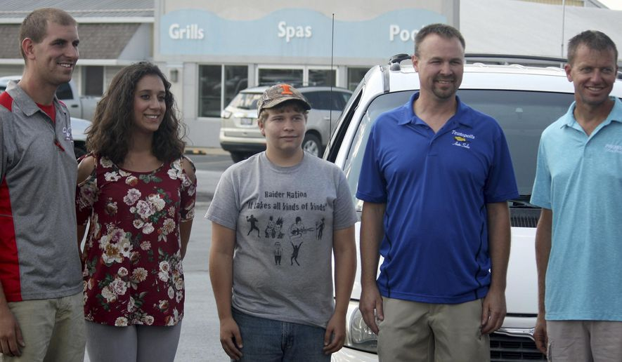 In this Sept. 9, 2017 photo, car dealers Wody Willenborg, left, Phil Webster, second from  right, and Mark Probst, right, award Brooke Daiber, a senior at St. Louis University, and Blake Barnes a Junior at Shelbyvill High School with used vehicles through the Wheels To Prosper program, in Effingham, Ill. The students are is part of the first CEO, (Creating Entrepreneurial Opportunities) class in Shelby County, a program that encourages entrepreneurship. (Graham Milldrum/Effingham Daily News via AP)