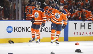Edmonton Oilers' Oscar Klefbom (77) and Connor McDavid (97) wait for hats to be picked up after Connor McDavid scored a hat trick against the Calgary Flames, during the third period of an NHL hockey game Wednesday, Oct. 4, 2017, in Edmonton, Alberta. (Jason Franson/The Canadian Press via AP)