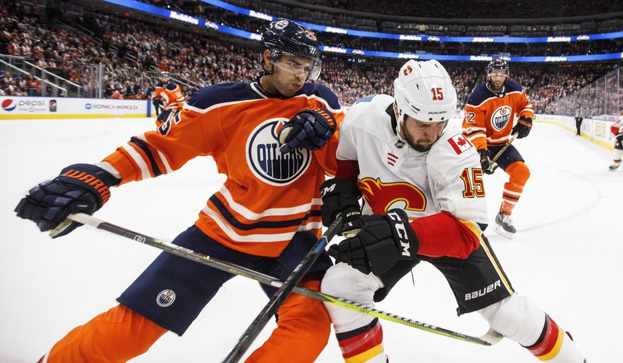 Calgary Flames' Tanner Glass (15) and Edmonton Oilers' Darnell Nurse (25) battle in the corner during the third period of an NHL hockey game Wednesday, Oct. 4, 2017, in Edmonton, Alberta. (Jason Franson/The Canadian Press via AP)