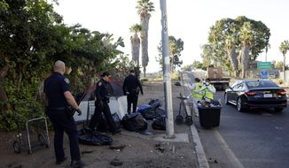 FILE - In this Sept. 25, 2017 file photo, police officers remove a tent left by the homeless during efforts to sanitize neighborhoods to control the spread of hepatitis A, in San Diego. Health officials say a deadly California outbreak of hepatitis A may take a year or more to abate. The liver-damaging illness has infected hundreds of people since last November, chiefly in San Diego, Santa Cruz and Los Angeles counties. Most cases and all 17 deaths occurred in San Diego County. Experts believe the highly contagious disease was spread by transients there to homeless populations around the state. (AP Photo/Gregory Bull,File)