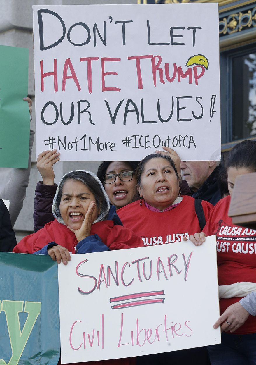FILE -- In this Jan. 25, 2017 file photo protesters hold signs as they yell at a rally outside of City Hall in San Francisco, Wednesday, Jan. 25, 2017. California Gov. Jerry Brown signed legislation, SB54, the statuary state bill, that extends protections statewide for immigrants living the United State illegally, Thursday, Oct. 5, 2017. (AP Photo/Jeff Chiu,file)