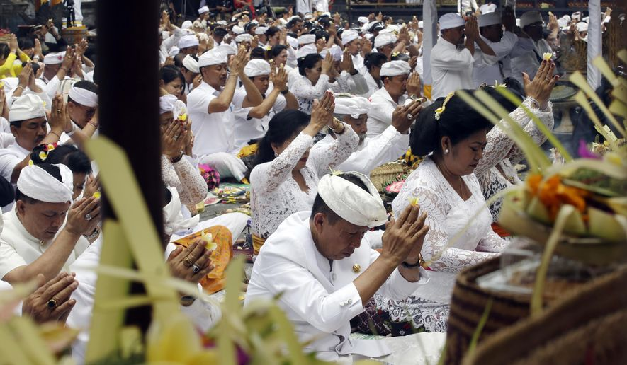 Bali Gov. Mangku Pastika, left in first row, prays with other Hindu worshipers during a ceremony at Besakih temple which is located few kilometers from the crater of Mount Agung volcano in Karangasem, Bali, Indonesia, Thursday, Oct. 5, 2017. More than 140,000 people have fled from the surrounds of Mount Agung since authorities raised the volcano's alert status to the highest level on Sept. 22 after a sudden increase in tremors. It last erupted in 1963, killing more than 1,000 people. (AP Photo/Firdia Lisnawati)