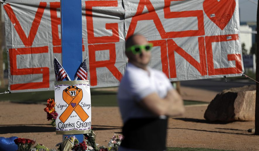 Gareth Wilkinson stands near a makeshift memorial in honor of the victims of a mass shooting Thursday, Oct. 5, 2017, in Las Vegas. (AP Photo/Gregory Bull)