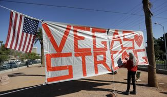Las Vegas resident Nancy Cooley signs a Vegas Strong banner honoring the victims of a mass shooting on Thursday, Oct. 5, 2017, in Las Vegas. A gunman opened fire on an outdoor music concert on Sunday killing dozens and injuring hundreds. (AP Photo/Gregory Bull)