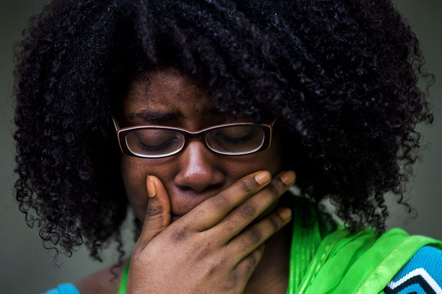 Alyssia Washington, 24, of Flint, Mich., gasps aloud as she tries to hold back tears while names of identified victims from the Las Vegas mass shooting are read aloud, while standing in a circle of more than 50 University of Michigan-Flint students and faculty members during a vigil at the McKinnon Plaza on campus Wednesday, Oct. 4, 2017 in downtown Flint. (Jake May/The Flint Journal-MLive.com via AP)
