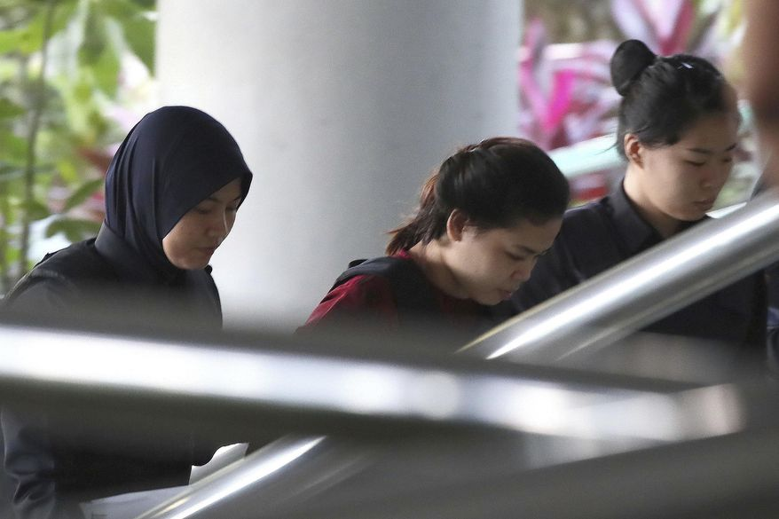 Indonesian Siti Aisyah, center, is escorted by police as she arrives for court hearing at Shah Alam court house in Shah Alam, outside Kuala Lumpur, Malaysia Thursday, Oct. 5, 2017.  Aisyah and Doan Thi Huong of Vietnam have pleaded not guilty to killing Kim Jong Nam on Feb. 13 at a crowded Kuala Lumpur airport terminal. They are accused of wiping VX on Kim's face in an assassination widely thought to have been orchestrated by North Korean leader Kim Jong Un. (AP Photo/Sadiq Asyraf)