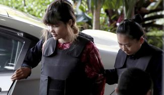 Vietnamese Doan Thi Huong, left, is escorted by police as she arrives for court hearing at Shah Alam court house in Shah Alam, outside Kuala Lumpur, Malaysia Thursday, Oct. 5, 2017. Doan and Siti Aisyah of Indonesia have pleaded not guilty to killing Kim Jong Nam on Feb. 13 at a crowded Kuala Lumpur airport terminal. They are accused of wiping VX on Kim's face in an assassination widely thought to have been orchestrated by North Korean leader Kim Jong Un. (AP Photo/Sadiq Asyraf)