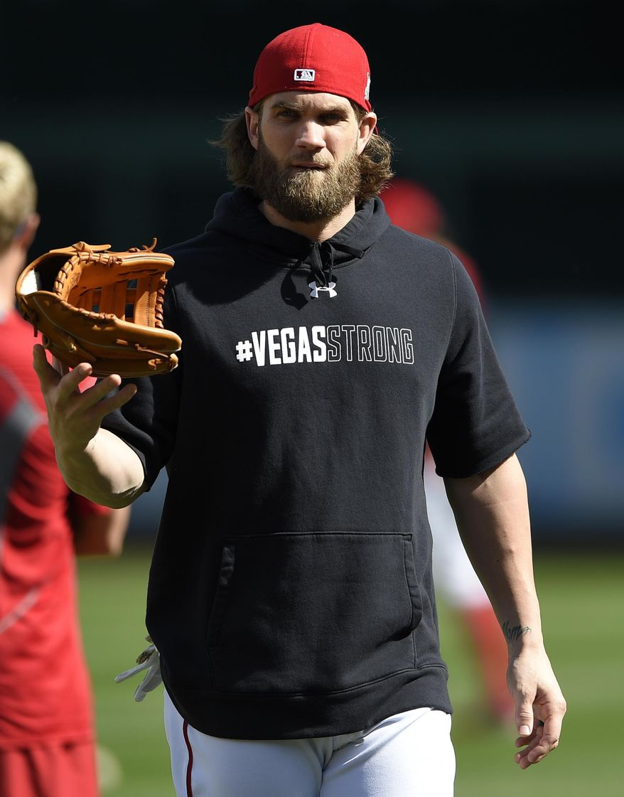 """Washington Nationals' Bryce Harper walks on the field wearing a """"#Vegas Strong"""" hoodie during baseball practice at Nationals Park, Thursday, Oct. 5, 2017, in Washington. The Nationals host the Chicago Cubs in Game 1 of the National League Division Series on Friday. (AP Photo/Nick Wass)"""