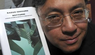 """FILE - In this Saturday, Aug 8, 2009 file photo, author Kazuo Ishiguro shows his book """"Nocturnals"""" before receiving the """"Giuseppe Tomasi di Lampedusa"""" prize for literature, in Santa Margherita Belice, near Palermo, Sicily, southern Italy.  The Nobel Prize for Literature for 2017 has been awarded to British novelist Kazuo Ishiguro, it was announced on Thursday, Oct. 5, 2017. (AP Photo/Alessandro Fucarini, File)"""
