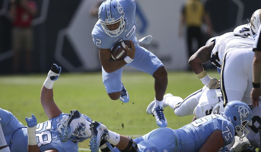 FILE - In this Sept. 30, 2017, file photo, North Carolina quarterback Chazz Surratt (12) jumps over offensive tackle Bentley Spain (75) as he runs the ball in the first half of an NCAA college football game against Georgia Tech in Atlanta. Surratt has started the past four games for the Tar Heels entering Saturday's game against No. 21 Notre Dame. (AP Photo/John Bazemore, File)