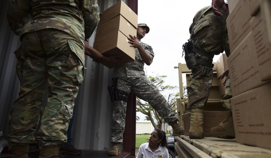 Soldiers and National Guard organize aid for the Santa Ana community in the aftermath of Hurricane Maria in Guayama, Puerto Rico, Thursday, Oct. 5, 2017. Even before the storm hit on Sept. 20, Puerto Rico was in dire condition thanks to a decade-long economic recession that had left its infrastructure in a sorry state. (AP Photo/Carlos Giusti)