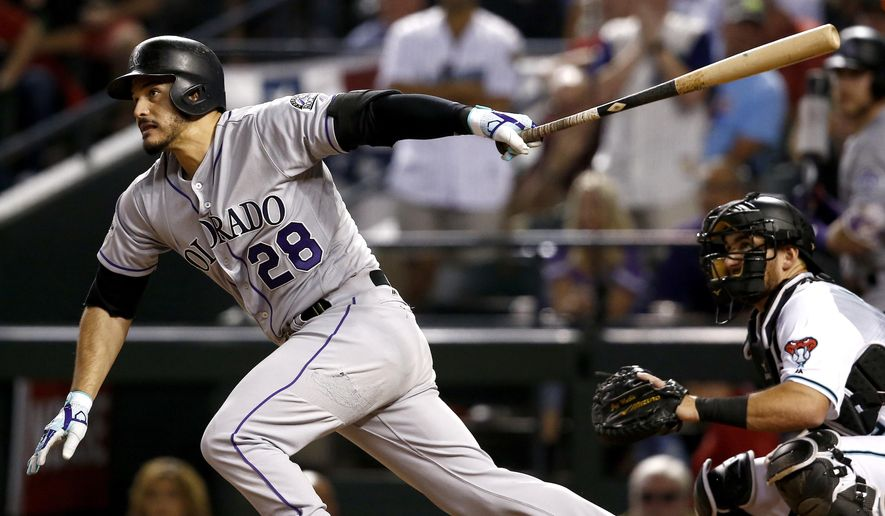 Colorado Rockies' Nolan Arenado follows through on a base hit against the Arizona Diamondbacks during the fourth inning of the National League wild-card playoff baseball game, Wednesday, Oct. 4, 2017, in Phoenix. (AP Photo/Ross D. Franklin)