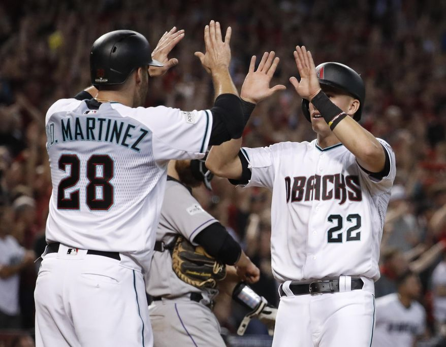 Arizona Diamondbacks' J.D. Martinez (28) high-fives Jake Lamb (22) after they scored on a two-run triple by A.J. Pollock during the eighth inning of the National League wild-card playoff baseball game against the Colorado Rockies, Wednesday, Oct. 4, 2017, in Phoenix. (AP Photo/Matt York)
