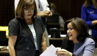 FILE - In this June 12, 2013, file photo, Catherine Miranda, D-Phoenix, right, talks with Debbie McCune Davis, D-Phoenix, in a special session budget battle for Medicaid funding in Phoenix. The Arizona Senate's ethics committee voted along party lines Thursday, Oct. 5, 2017 to investigate a Democratic lawmaker who is accused of circulating a petition to repeal a new school voucher expansion bill when it wasn't properly filled out. The five-member panel controlled by majority Republicans voted against dismissing the complaint against Sen. Catherine Miranda. Miranda attorney Tom Ryan called the move a political payback for her vote against school vouchers. (AP Photo/Ross D. Franklin, File)