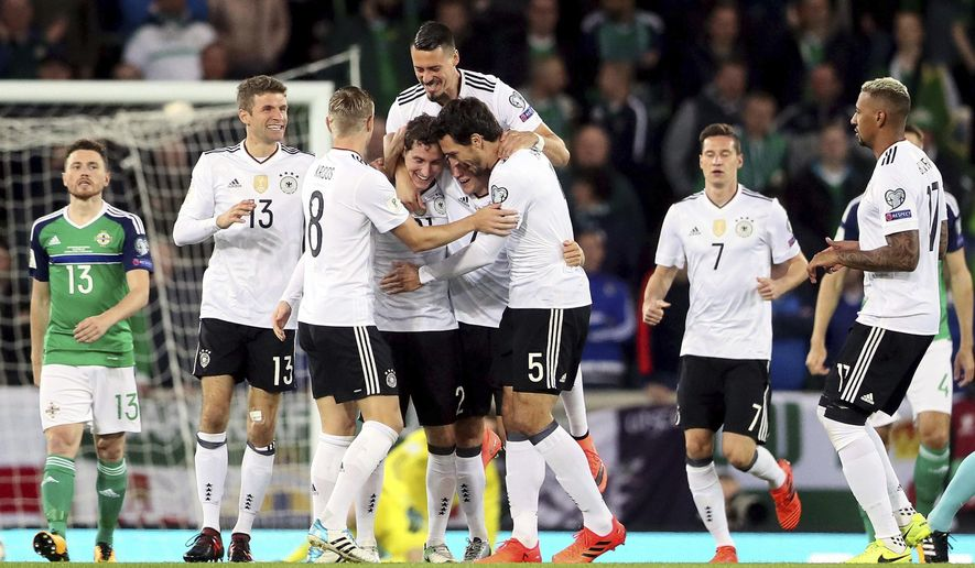 Germany's Sebastian Rudy, fourth from left, celebrates scoring his side's first goal of the game with his team-mates during the World Cup Group C qualifying soccer match between Germany and Northern Ireland at Windsor Park, Belfast, Northern Ireland. Thursday, Oct. 5, 2017. (Brian Lawless/PA via AP)