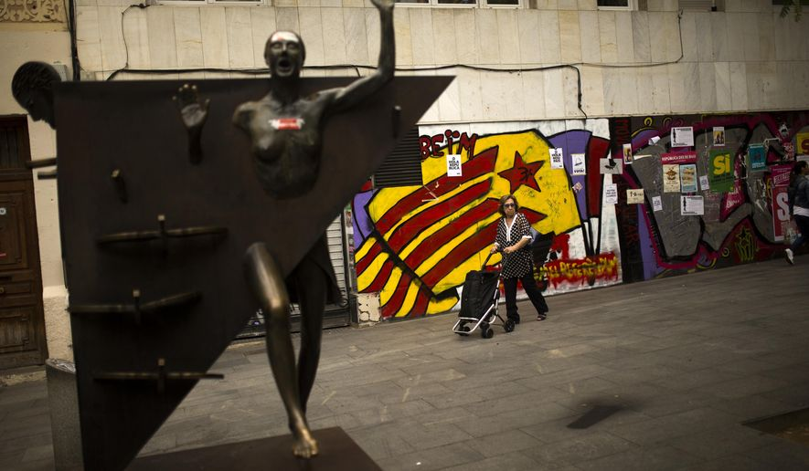 "A woman pushes a trolley past a graffiti of an ""estelada"", or Catalonia independence flag, at the Gracia neighborhood in Barcelona, Wednesday, Oct. 4, 2017. Catalonia's regional government is mulling when to declare the region's independence from Spain in the wake of a disputed referendum that has triggered Spain's most serious national crisis in decades. (AP Photo/Francisco Seco)"